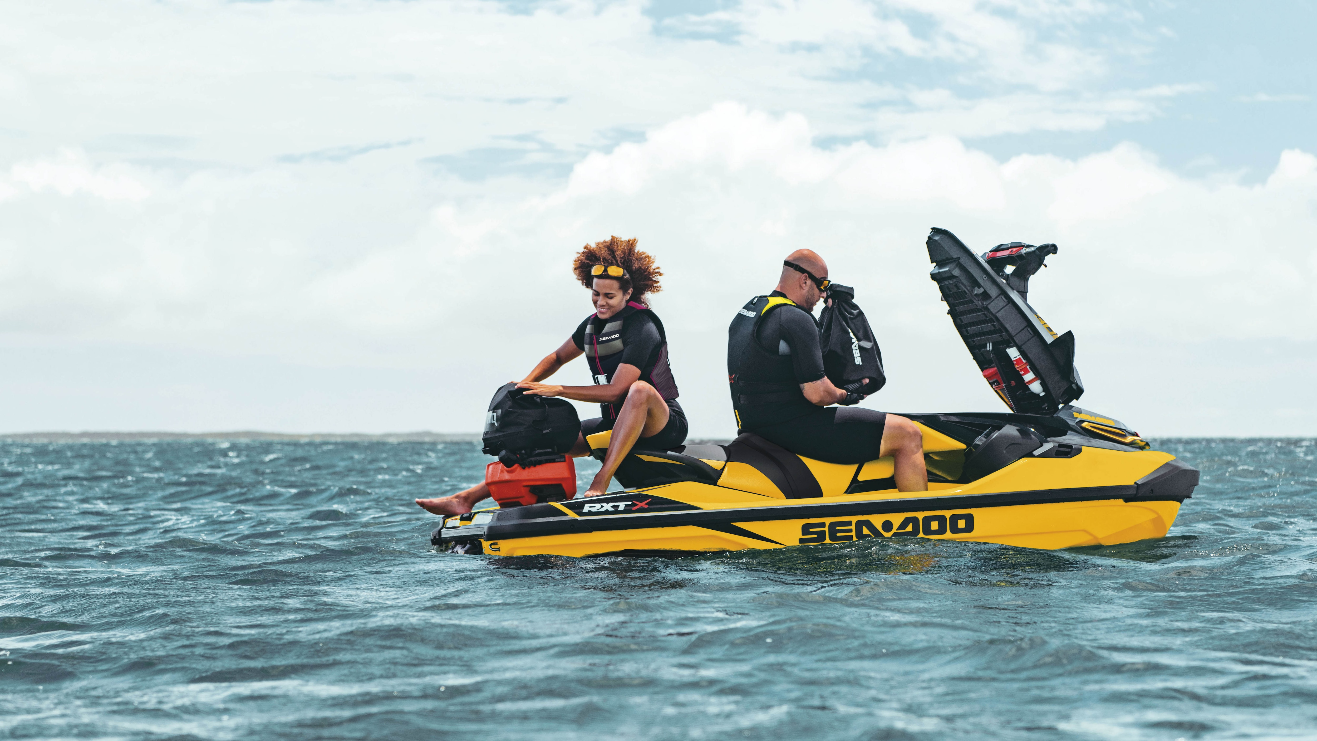 Couple storing bags in a Sea-Doo RXT-X
