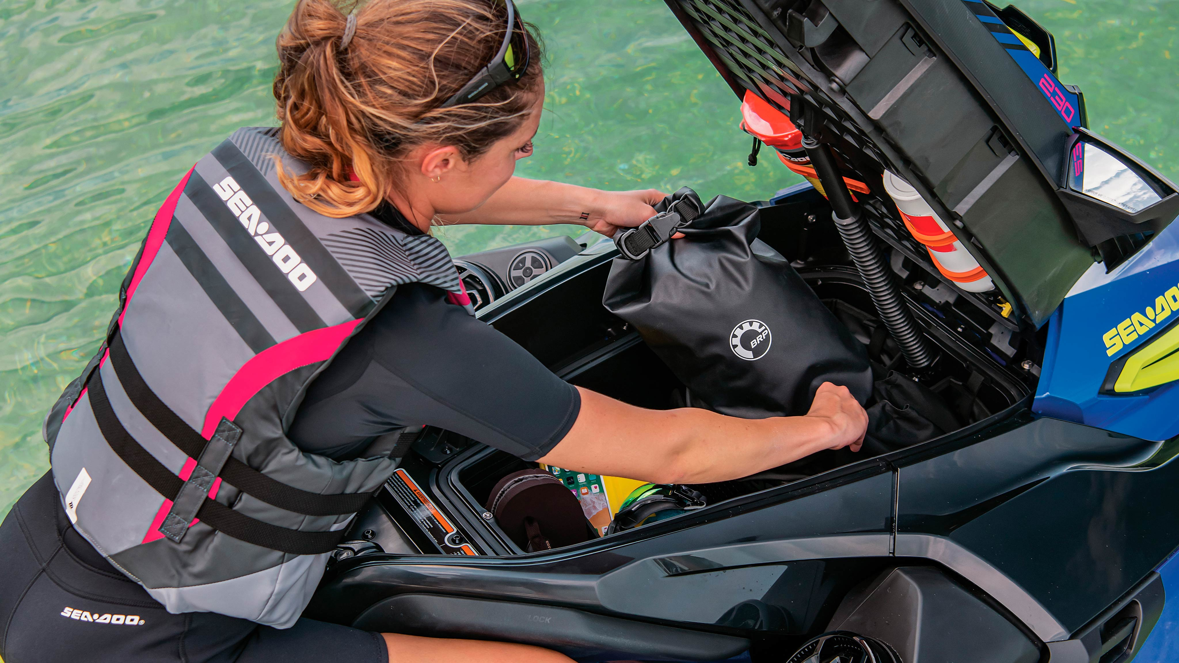 Woman using ingenious storage on her Sea-Doo Wake Pro