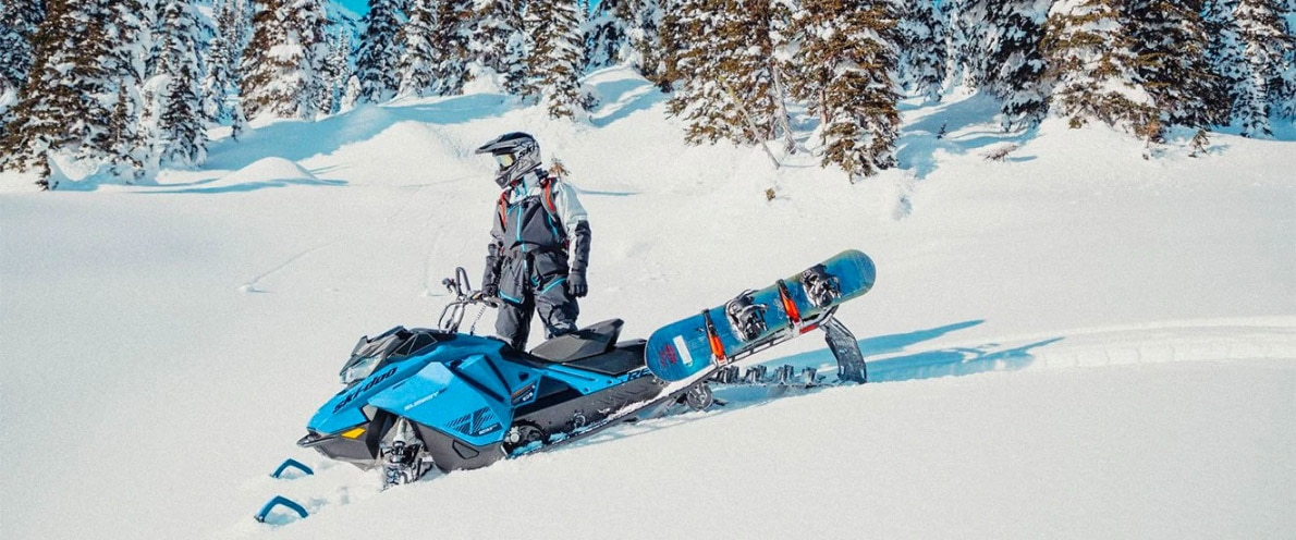 Man near his Ski-Doo Summit and his snowboard