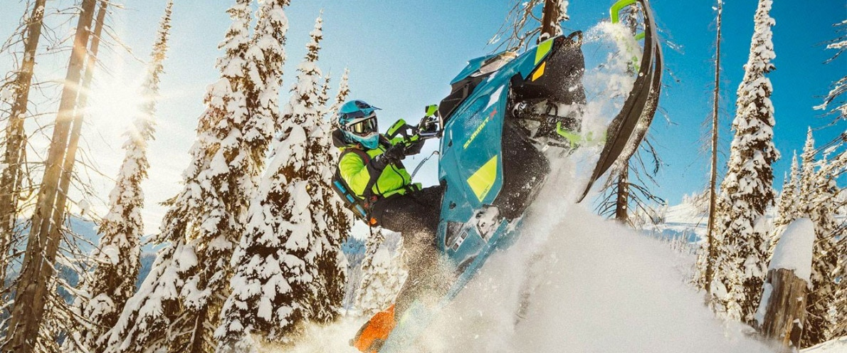 Wide angle of a Man jumping through the air on his Ski-Doo Summit