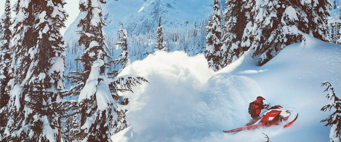 Man drifting in snow with his Summit snowmobile