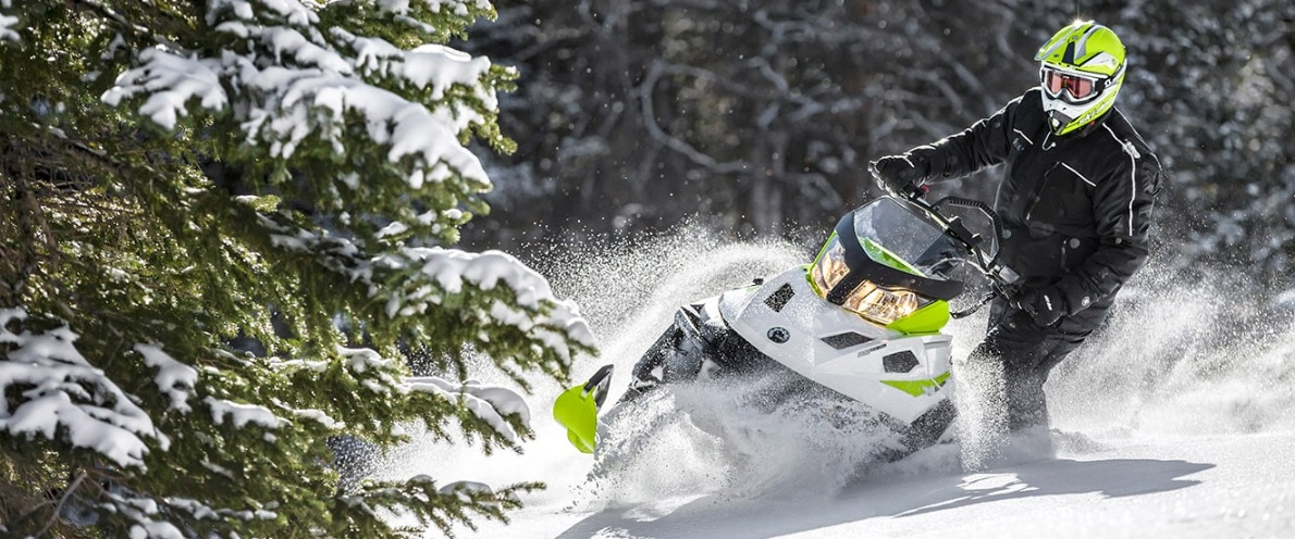 Man standing up while turning his Ski-Doo Tundra snowmobile