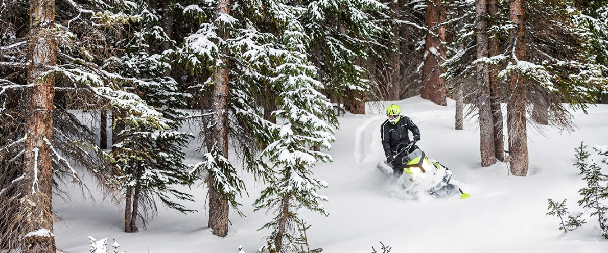 Man going down a small snowy trail with his Ski-Doo Tundra