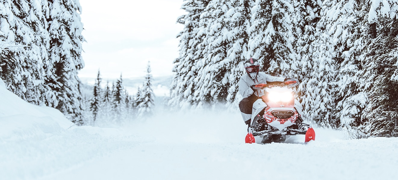 Man driving a Ski-Doo Backcountry though a snowy forest trail