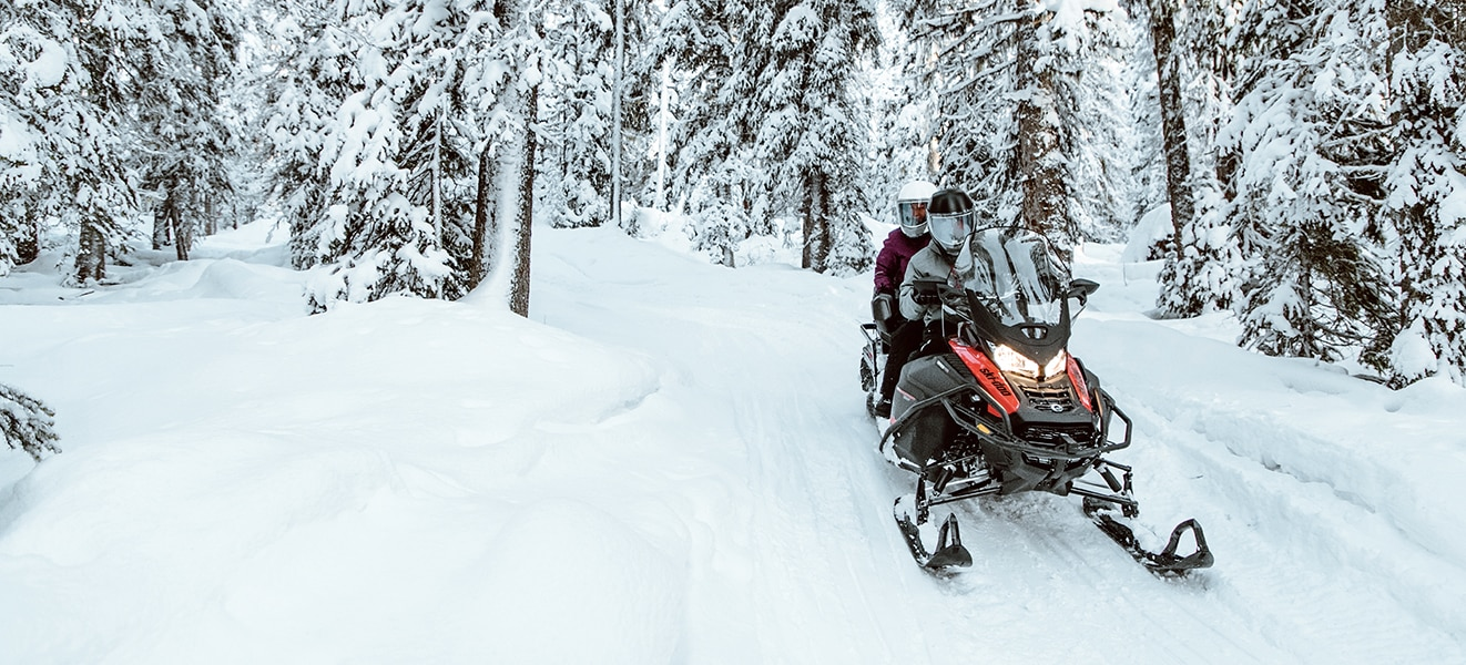 A couple driving a Ski-Doo Expedition through a snowy forest trail