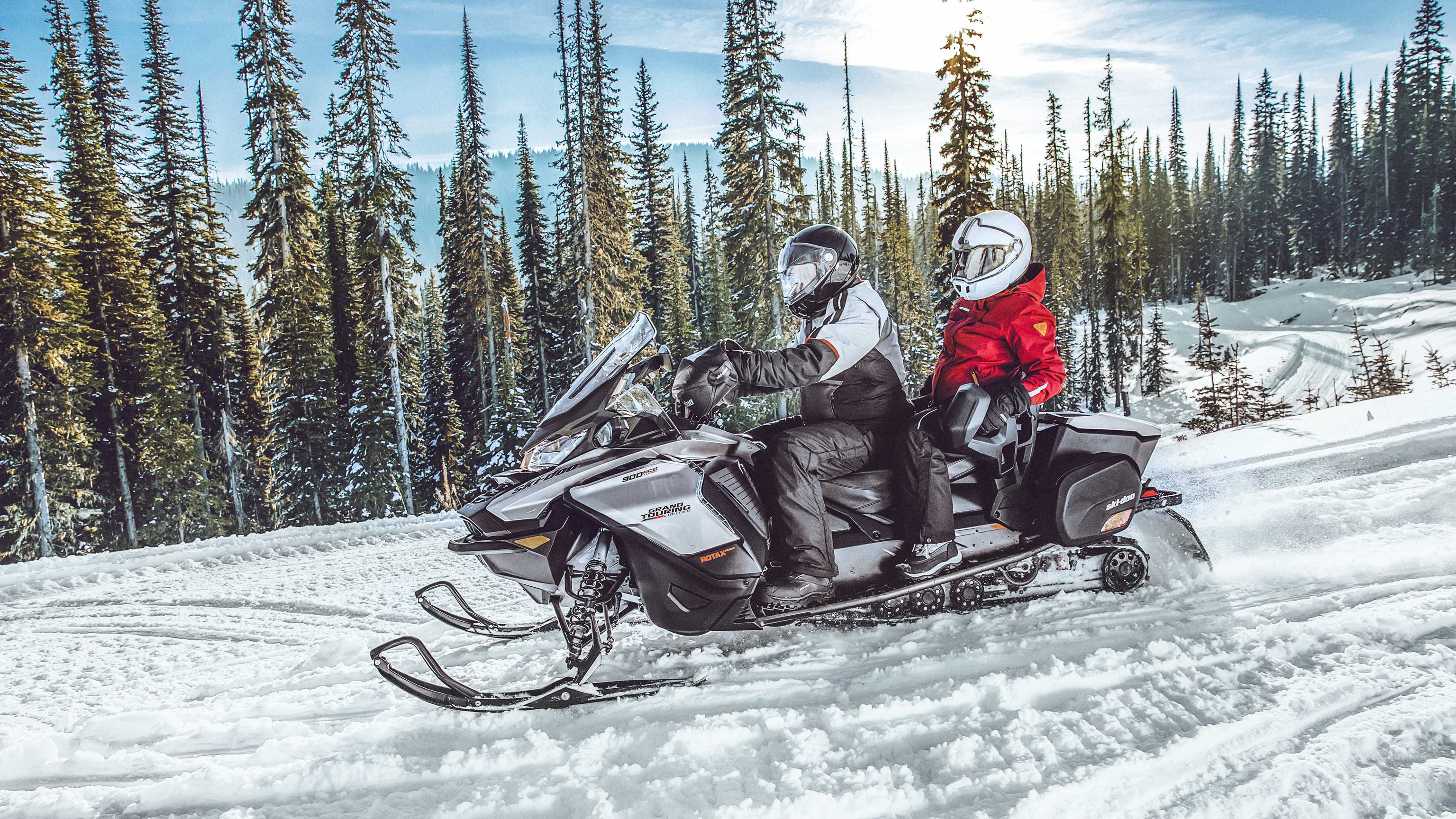Couple riding 2022 Ski-Doo grand Touring snowmobile