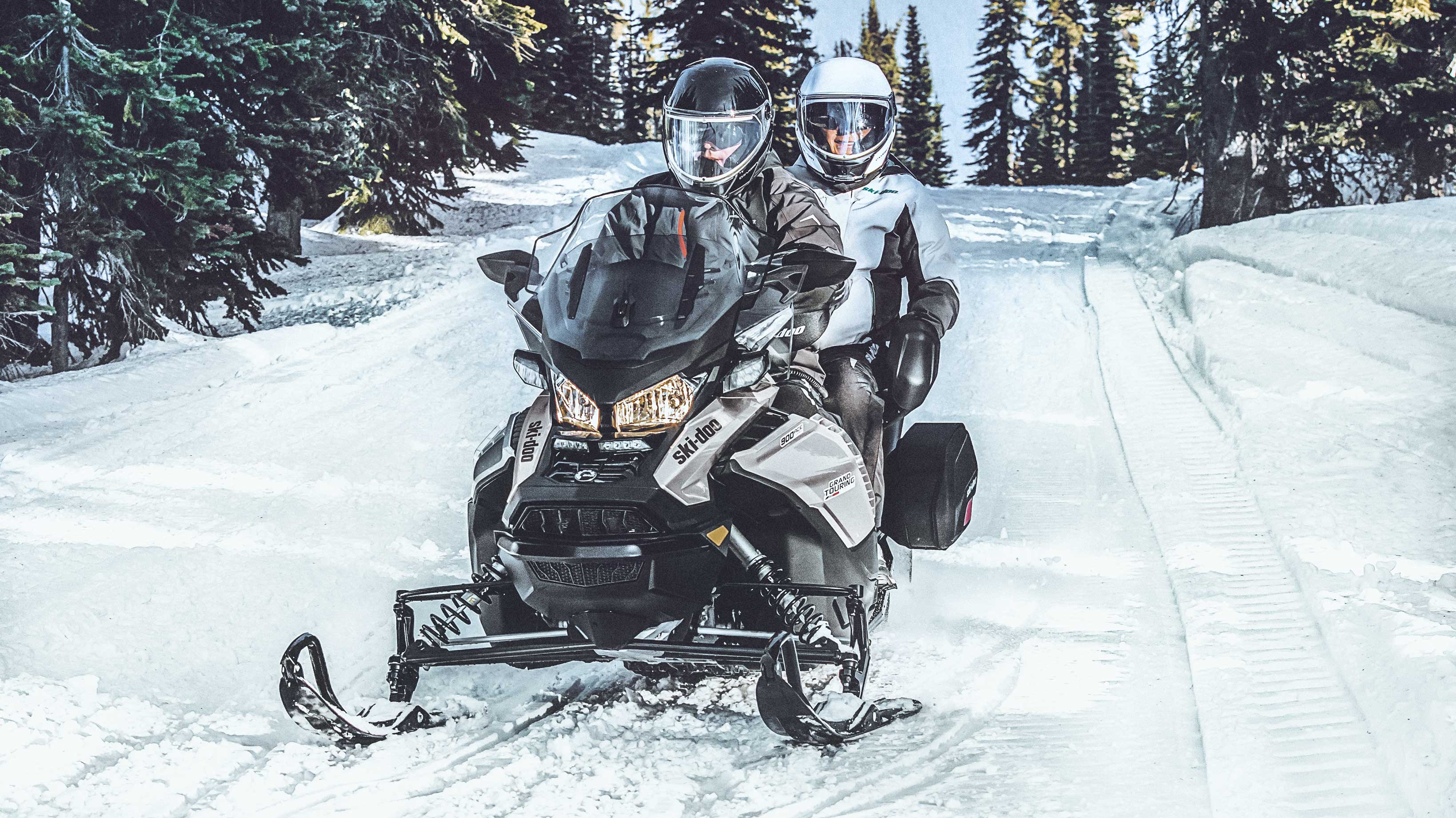 Couple & their 2022 Ski-Doo grand Touring on a trail